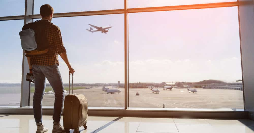 Man With Luggage Standing At Airport Window Looking Airplane Thinking About Travel Essentials