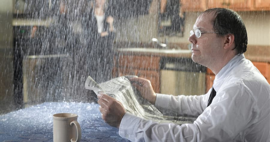 Rain Leaking On Man At Table During Storms